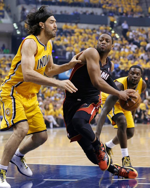 . Miami Heat\'s Dwyane Wade goes to the basket against Indiana Pacers\' Luis Scola during the first half of Game 2 of the NBA basketball Eastern Conference finals in Indianapolis, Tuesday, May 20, 2014. (AP Photo/Michael Conroy)