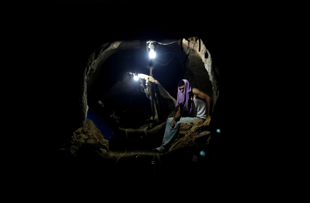 . In this Monday, Sept. 30, 2013 photo, a Palestinian worker rests inside a smuggling tunnel in Rafah, on the border between Egypt and the southern Gaza Strip. Since the summer, Egyptís military has tried to destroy or seal off most of the smuggling tunnels under the Gaza-Egypt border, a consequence of the heightened tensions between Cairo and the Hamas government in Gaza. The tunnels once employed thousands of young men in Gaza. By early September, with most tunnels closed, only few tunnel workers reported to their jobs for maintenance work. Some mask their faces with shirts to avoid identification while working, for fear of repercussions in case they were to travel to Egypt in the future. (AP Photo/Hatem Moussa)
