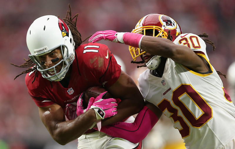 . Wide receiver Larry Fitzgerald #11 of the Arizona Cardinals carries the football past free safety E.J. Biggers #30 of the Washington Redskins en route to scoring a 24 yard touchdown reception during the second quarter of the NFL game at the University of Phoenix Stadium on October 12, 2014 in Glendale, Arizona.  (Photo by Christian Petersen/Getty Images)
