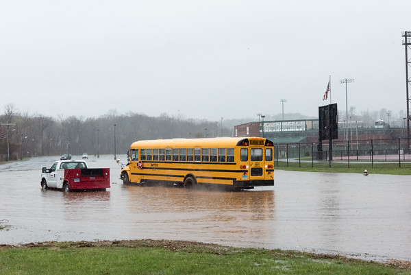 04/16/18 Wesley Bunnell | Staff A DATTCO fleet vehicle pulls alongside of a school bus stuck in floodwater at Willow Brook Park on Monday afternoon. The bus was eventually able to free itself with assistance after approximately 20 minutes.