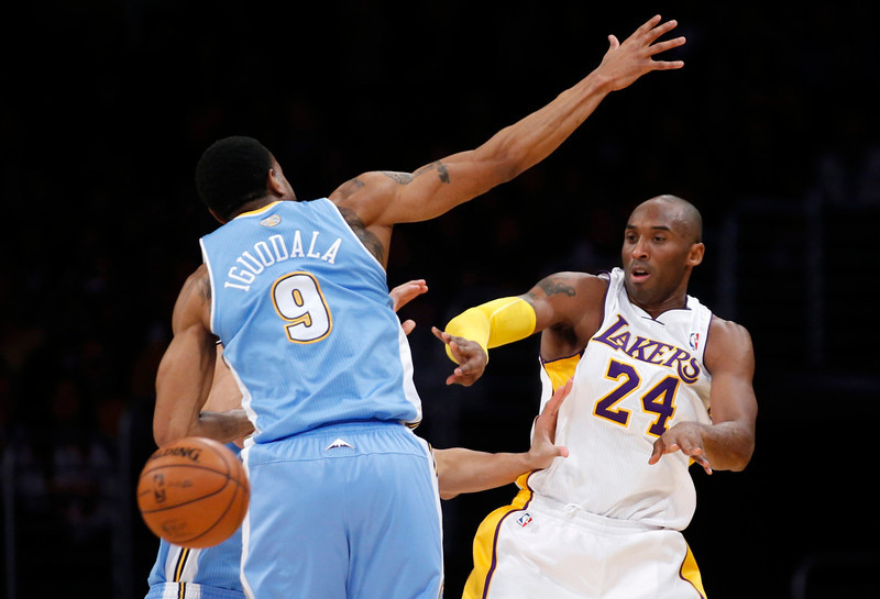 . Los Angeles Lakers\' Kobe Bryant (R) passes the ball around Denver Nuggets\' Andre Iguodala during the first half of their NBA basketball game in Los Angeles January 6, 2013. REUTERS/Danny Moloshok