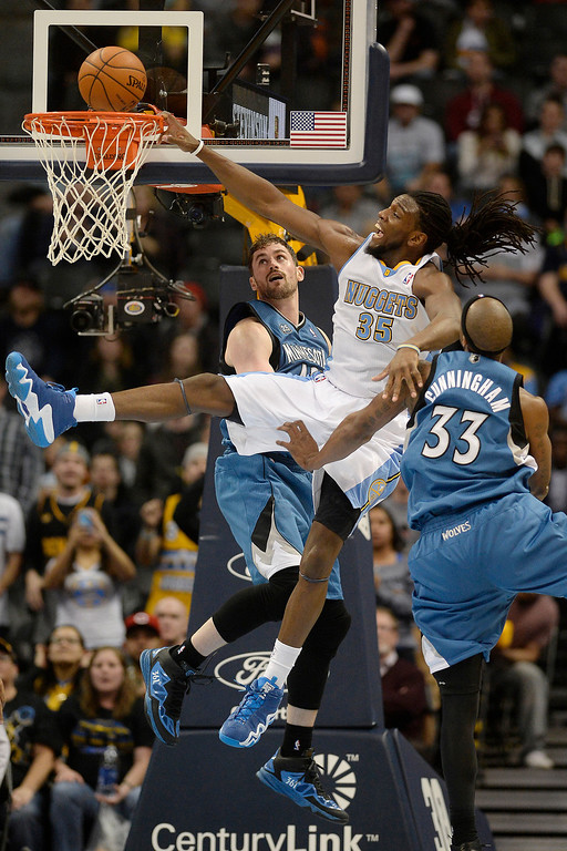 . Dante Cunningham (33) of the Minnesota Timberwolves fouls Kenneth Faried (35) of the Denver Nuggets as Kevin Love (42) of the Minnesota Timberwolves gives help on the defensive effort during the second hal. (Photo By AAron Ontiveroz/The Denver Post)