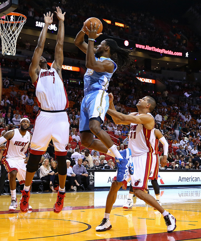 . MIAMI, FL - MARCH 14: J.J. Hickson #7 of the Denver Nuggets shoots over Chris Bosh #1 of the Miami Heat during a game  at American Airlines Arena on March 14, 2014 in Miami, Florida. (Photo by Mike Ehrmann/Getty Images)
