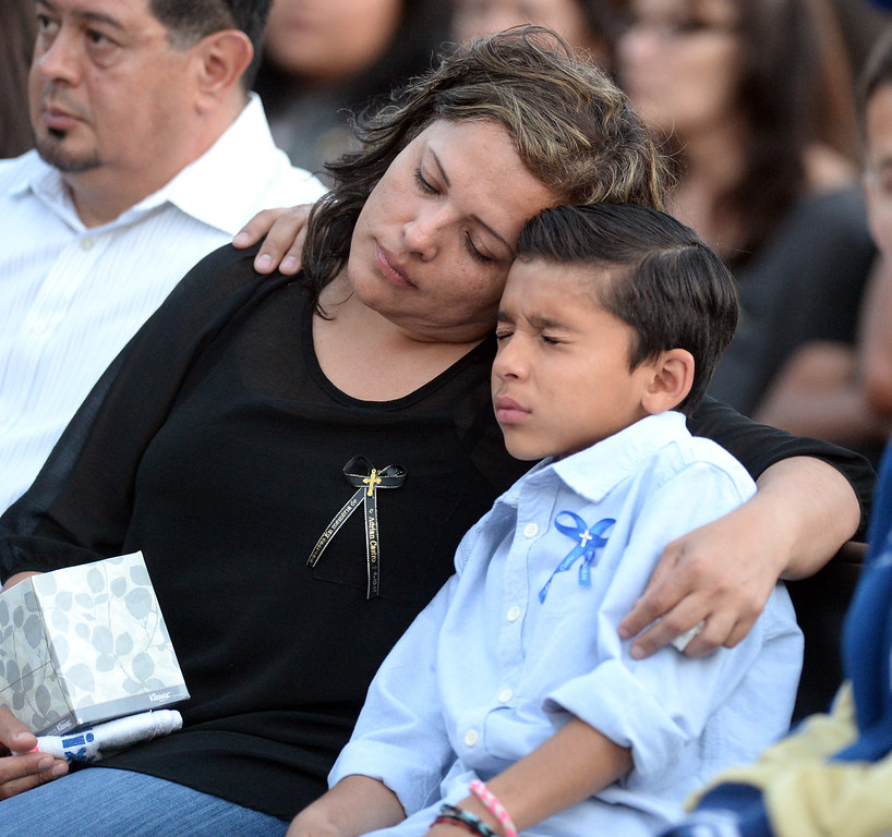 . Veronica Soriano, mother of Adrian Castro, 19, holds her youngest son, Solan, 10, during a memorial gathering for him at El Monte High School Monday evening April 14, 2014. Castro was one of nine students killed in the bus crash in Orland, Calif. (Staff Photo by Keith Durflinger/San Gabriel Valley Tribune)