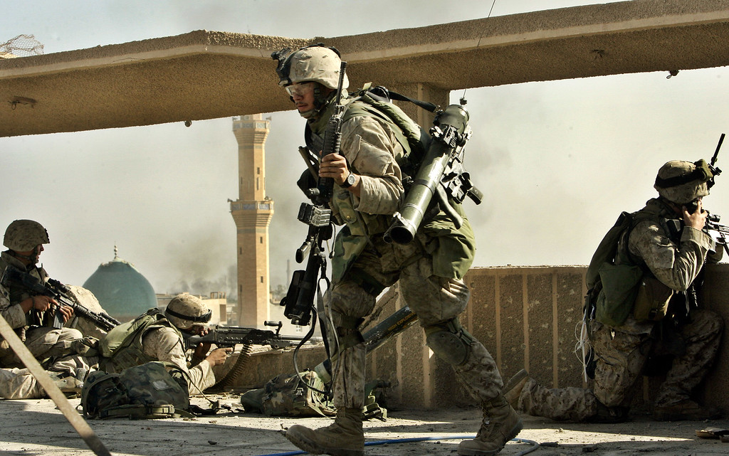 . US Marines take up position after coming under attack in the western part of Fallujah, Iraq, Saturday, Nov. 13, 2004. About 80 percent of the city was said to be under U.S. control, with insurgents pushed into a narrow corner. (AP Photo/Anja Niedringhaus)