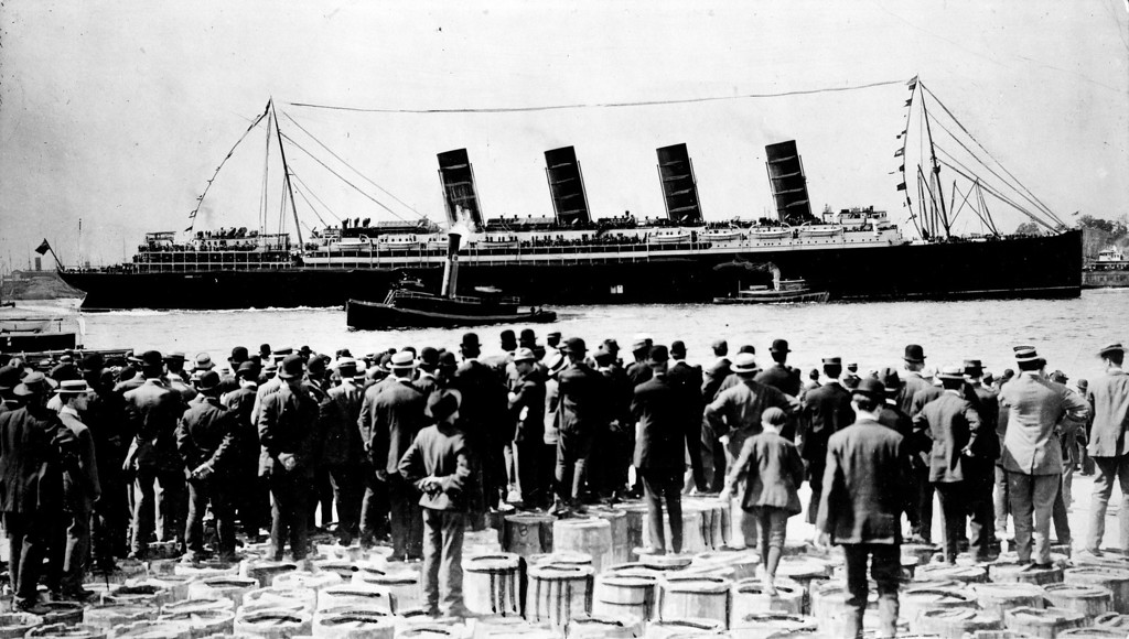 . RMS Lusitania, New York City, September 1907, stern-side view, during maiden voyage, with a large crowd of men, in foreground, standing on top of barrels. Library of Congress