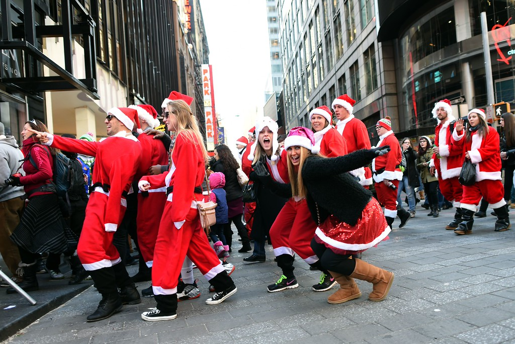 . People dressed as Santa Claus and Mrs. Claus arrive in Times Square as hundreds of Santas gather for the annual Santacon festivities on December 13, 2014 in New York. AFP PHOTO/DON  EMMERT/AFP/Getty Images
