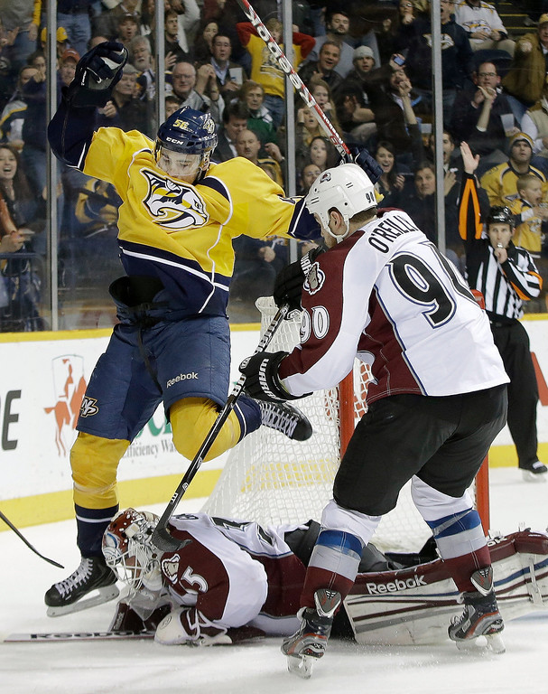 . Nashville Predators forward Taylor Beck (56) jumps over Colorado Avalanche goalie Jean-Sebastien Giguere (35) as Avalanche forward Ryan O\'Reilly (90) watches for a rebound in the second period of an NHL hockey game Tuesday, April 2, 2013, in Nashville, Tenn. (AP Photo/Mark Humphrey)