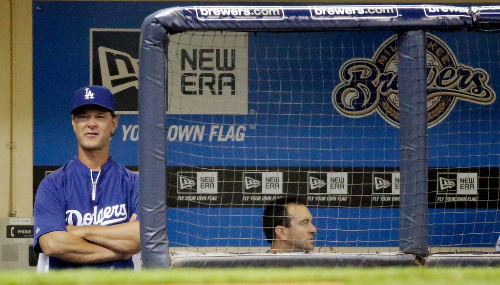 . Los Angeles Dodgers manager Don Mattingly watches from the dugout during the first inning of a baseball game against the Milwaukee Brewers Wednesday, May 22, 2013, in Milwaukee. (AP Photo/Morry Gash)