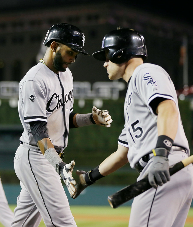 . Chicago White Sox\'s Alexei Ramirez, left, is congratulated by Gordon Beckham after scoring on a sacrifice hit by teammate Dayan Viciedo during the seventh inning of a baseball game against the Detroit Tigers, Wednesday, July 30, 2014 in Detroit. (AP Photo/Carlos Osorio)