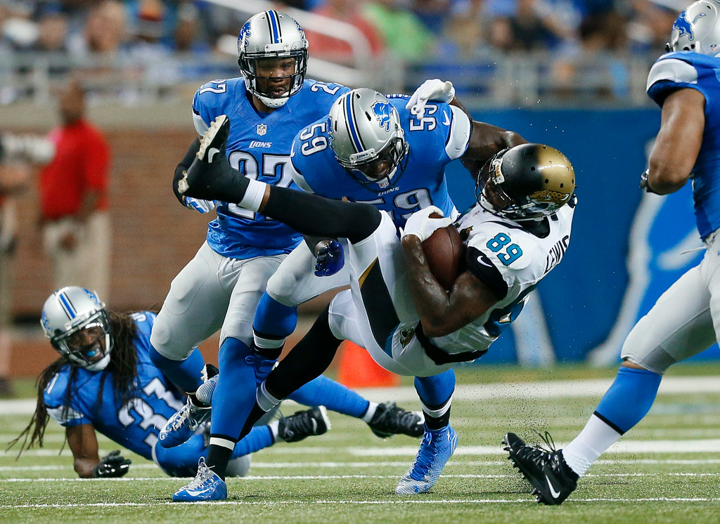 . Jacksonville Jaguars tight end Marcedes Lewis (89) is brought down by Detroit Lions linebacker Tahir Whitehead (59) in the first half of a preseason NFL football game at Ford Field in Detroit, Friday, Aug. 22, 2014. (AP Photo/Rick Osentoski)