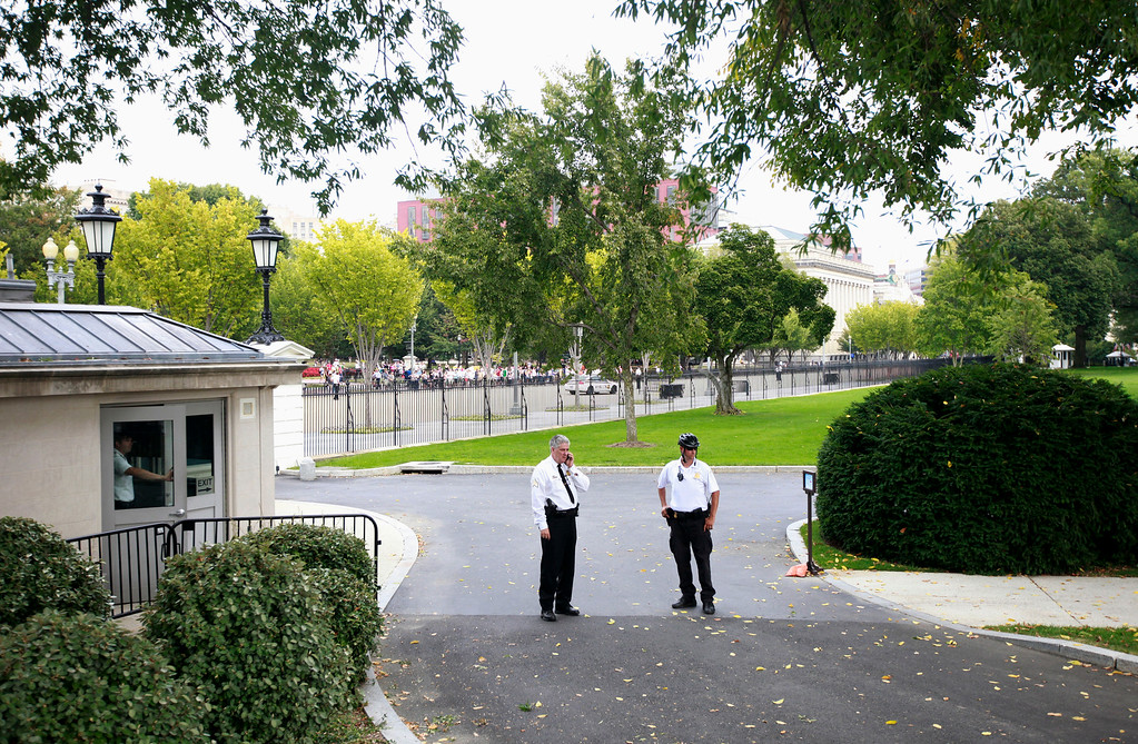 . Members of the uniform division of the Secret Service stand in the driveway of the White House in Washington, Thursday, Oct. 3, 2013, as access to Pennsylvania Ave., was temporarily denied, after reports of shots on Capitol Hill. (AP Photo/Pablo Martinez Monsivais)