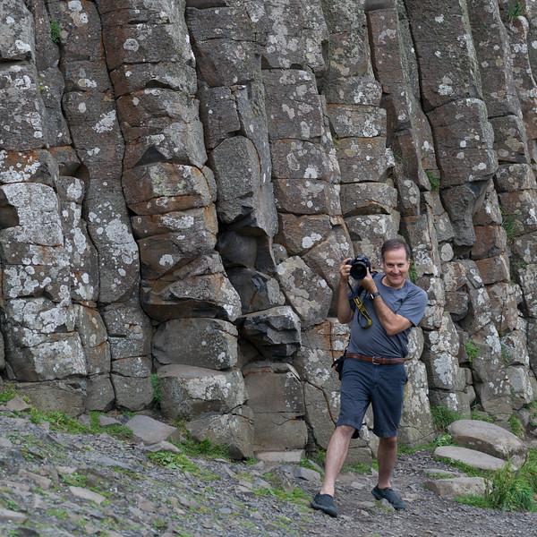 Photographer in front of basalt rocks, Giants Causeway, County Antrim, Northern Ireland, United Kingdom