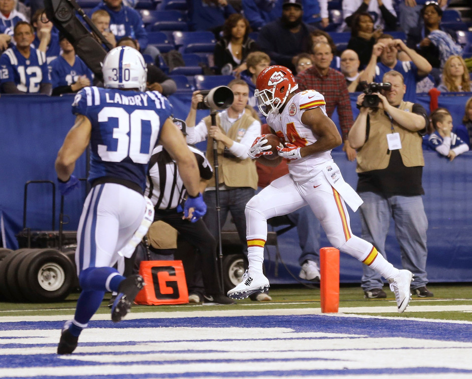 . Kansas City Chiefs\' Knile Davis (34) makes a 10-yard touchdown reception as Indianapolis Colts strong safety LaRon Landry (30) moves in during the second half of an NFL wild-card playoff football game Saturday, Jan. 4, 2014, in Indianapolis. (AP Photo/Michael Conroy)