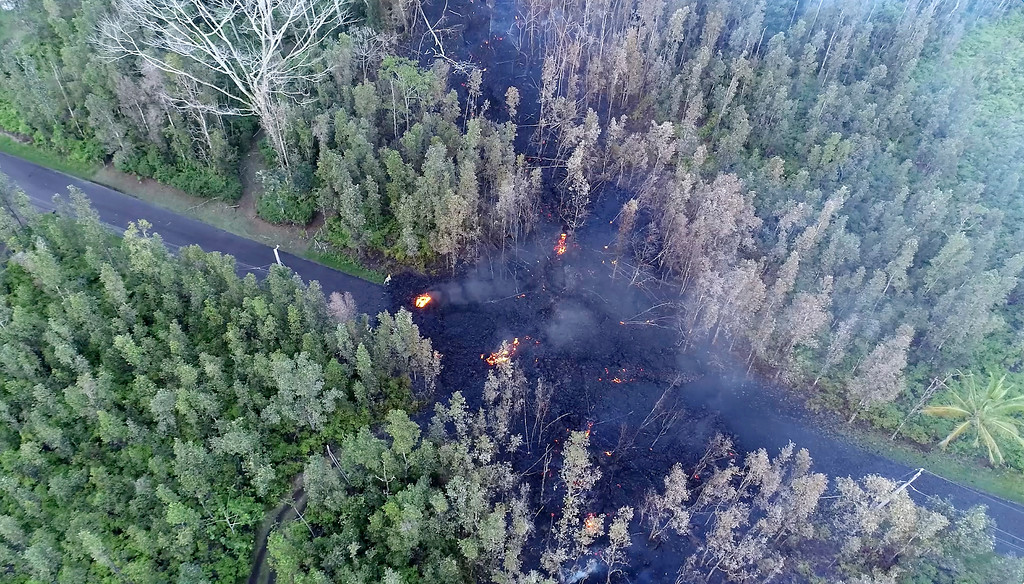. In this still frame taken from video, lava flows over a road in the Puna District as a result of the eruption from Kilauea Volcano on Hawaii\'s Big Island Friday, May 4, 2018. The eruption sent molten lava through forests and bubbling up from paved streets and forced the evacuation of about 1,500 people who were still out of their homes Friday after Thursday\'s eruption. (Byron Matthews via AP)