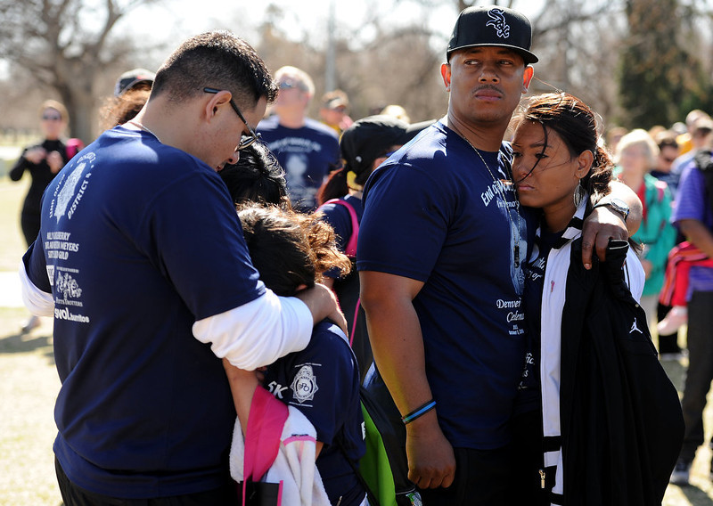 . As the doves were released family and friends remember their fallen comrade.  At left is DPD officer Rick Beall hugging daughter Alexis, 11.  At right is Officer  Everettt Moore and his wife Pam.  Family, colleagues, and friends of slain Denver Police Officer Celena Hollis turned out April 7, 2013 for a 5k run and walk to raise money for a scholarship fun and a memorial bench in City Park in Denver, CO.  Over 300 runners and walkers participated in the race that started at 9:00 am.  The race looped around City Park.  After the race, a gathering was held to remember Hollis and 22 white doves were released in her memory.  (Photo By Helen H. Richardson/ The Denver Post)