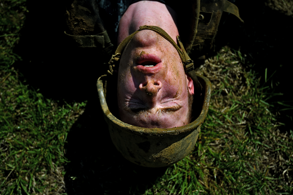 . A member of the United States Naval Academy freshman class shows his exhaustion at the wet and sandy station during the annual Sea Trials training exercise at the U.S. Naval Academy on May 13, 2014 in Annapolis, Maryland. (Photo by Patrick Smith/Getty Images)