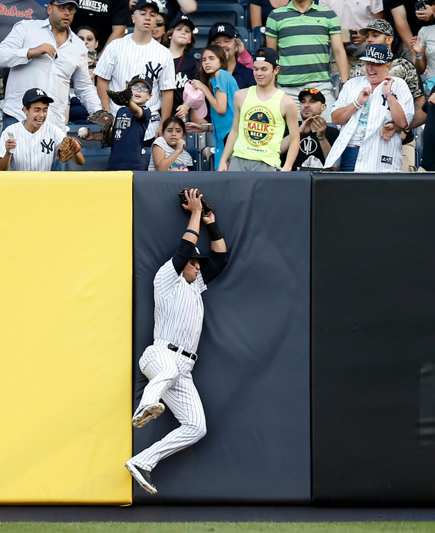 . New York Yankees right fielder Martin Prado catches Miguel Cabrera\'s first -inning sacrifice fly at the wall in a baseball game against the Detroit Tigers at Yankee Stadium in New York, Wednesday, Aug. 6, 2014.  Rajai Davis scored on the play. (AP Photo/Kathy Willens)