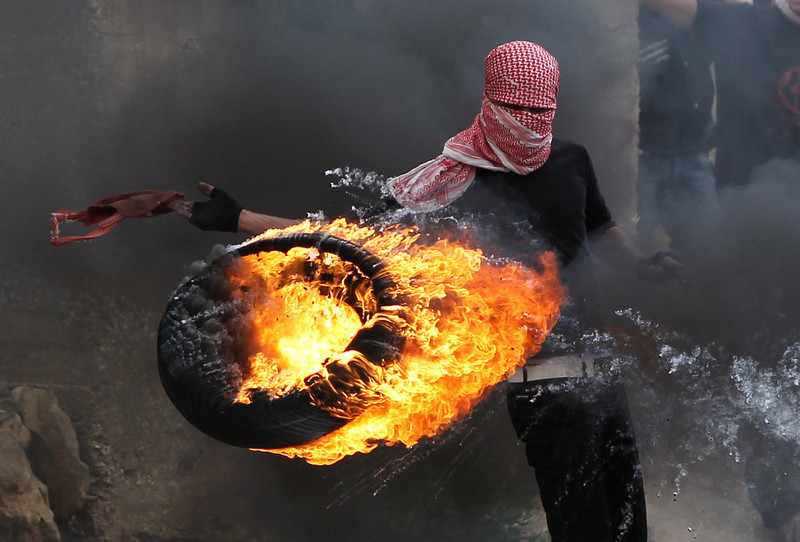". A Palestinian sets fire to a tyre during clashes between hundreds of Palestinians and Israeli soldiers outside the Ofer prison after a march marking the 65th Nakba day or ""Day of Catastrophe\"" on May 15, 2013 in Betunia near the West Bank city of Ramallah.  ABBAS MOMANI/AFP/Getty Images"