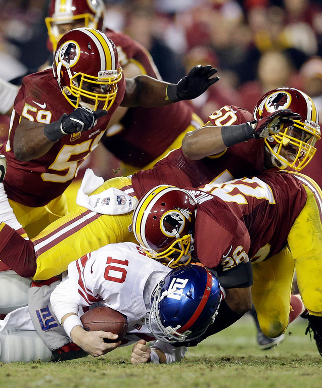 . New York Giants quarterback Eli Manning (10) is sacked by Washington Redskins inside linebacker London Fletcher (59), outside linebacker Rob Jackson (50)  and cornerback Josh Wilson during the second half of an NFL football game Sunday, Dec. 1, 2013, in Landover, Md. The Giants won 24-17. (AP Photo/Patrick Semansky)