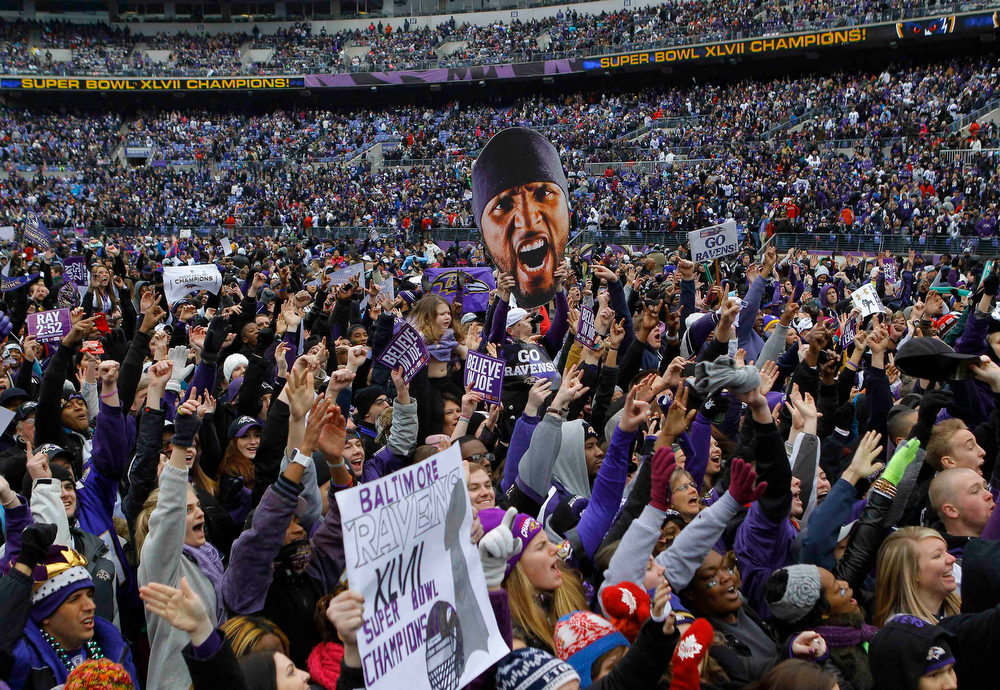 . Fans of Super Bowl XLVII champion Baltimore Ravens celebrate their victory before a stadium rally in Baltimore February 5, 2013. The Ravens defeated the San Francisco 49ers to win the NFL championship. The player cut-out (C) is of retiring Ravens\' linebacker Ray Lewis.    REUTERS/Gary Cameron