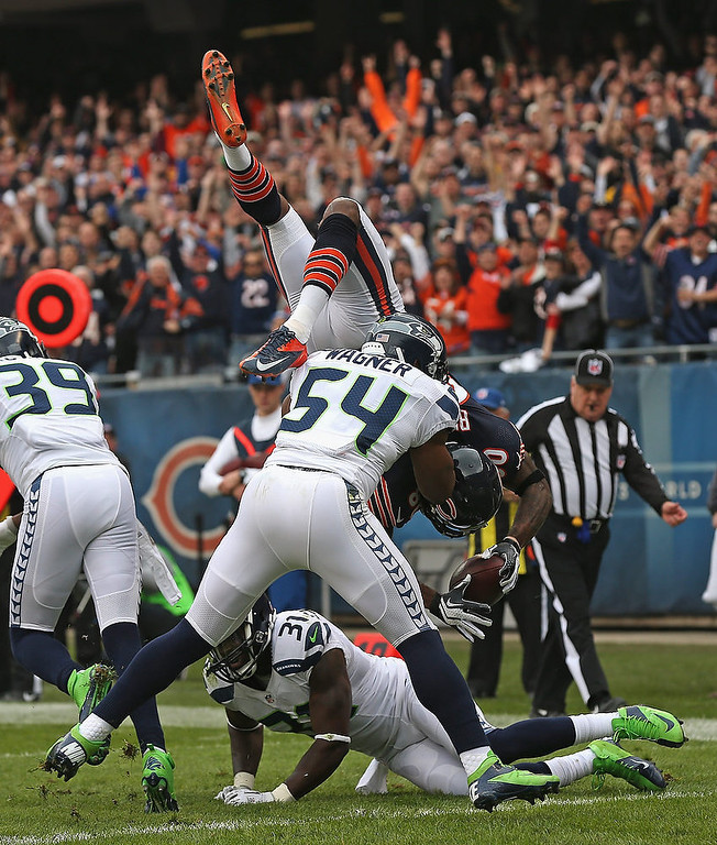 . Earl Bennett #80 of the Chicago Bears flips over Bobby Wagner #54 and Kam Chancellor #31 of the Seattle Seahawks to score a touchdown at Soldier Field on December 2, 2012 in Chicago, Illinois.  (Photo by Jonathan Daniel/Getty Images)