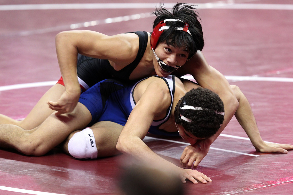 . James Logan\'s Jacob Macalolooy, top, wrestles Beaumont\'s Terrill Sidener in a 138-pound third round match during the California Interscholastic Federation wrestling championships in Bakersfield, Calif., on Friday, March 1, 2013. Macalolooy would go onto win. (Anda Chu/Staff)