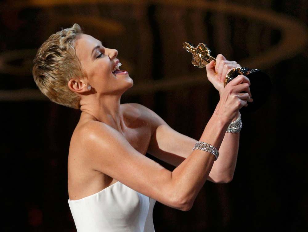 Description of . Charlize Theron holds the award before presenting it to Quentin Tarantino for best original screenplay for