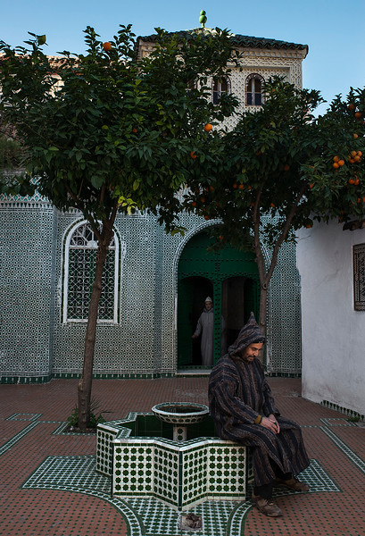 man sits outside a mosque in the blue town of Chefchaouen.  Morocco, 2018