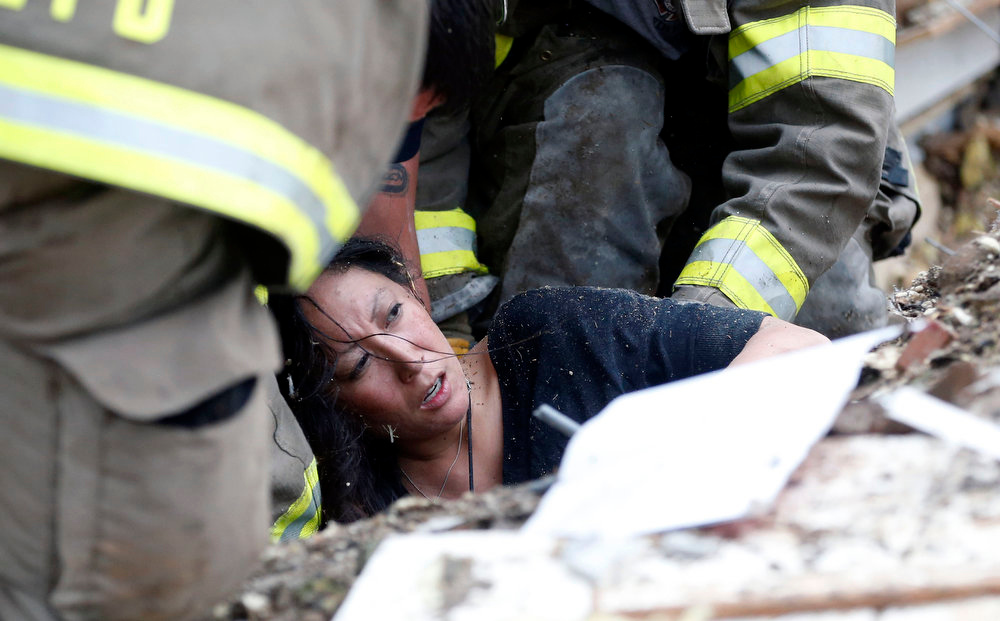. A woman is pulled out from under tornado debris at the Plaza Towers School in Moore, Okla., Monday, May 20, 2013. A tornado as much as a mile (1.6 kilometers) wide with winds up to 200 mph (320 kph) roared through the Oklahoma City suburbs Monday, flattening entire neighborhoods, setting buildings on fire and landing a direct blow on an elementary school. (AP Photo Sue Ogrocki)