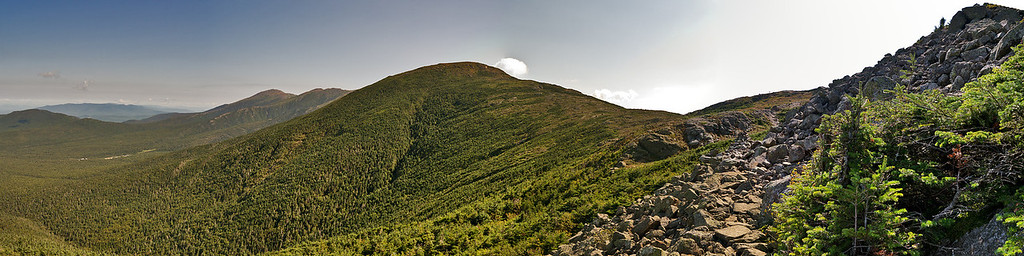 Edmands Path emerges along the north slope of Mt Eisenhower, heading toward a junction with the Crawford Path just ahead.   Mt Franklin (5001 ft) is left center, Mt Eisenhower is to the right, not shown.   The strip of white down among the trees to the left is the Mt Washington Cog Railway base station.   The Cog runs along the ridge beyond Mt Franklin to the 6288 foot summit of Mt Washington, hidden behind Mt Franklin from this vantage point.